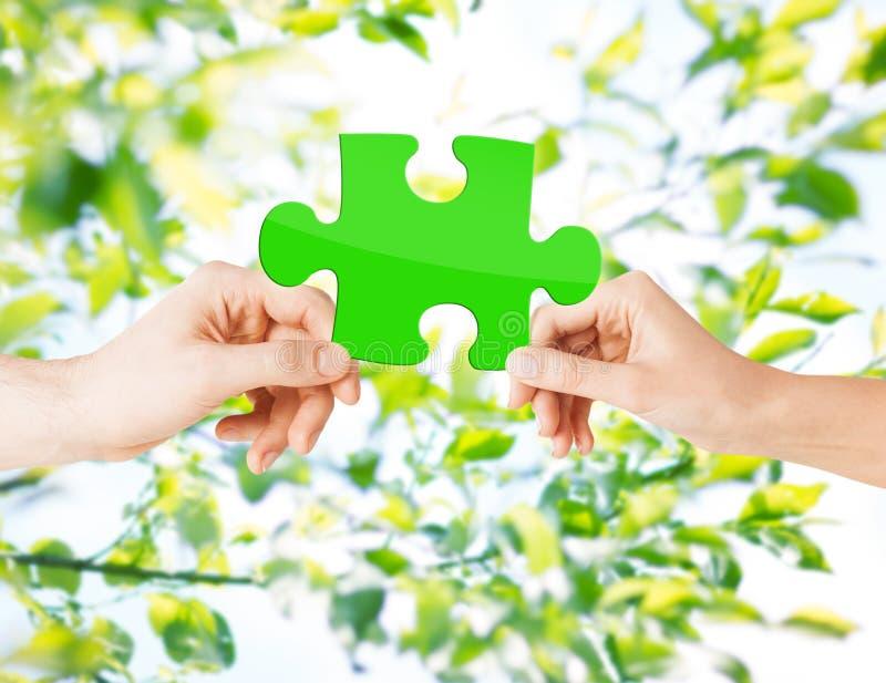 Manos con rompecabezas verde sobre fondo natural fotografía de archivo