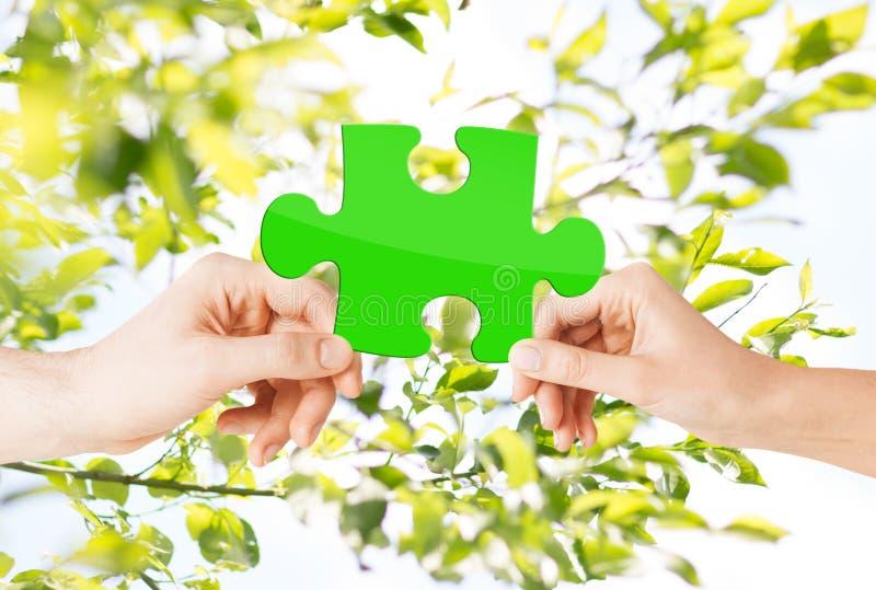Manos con rompecabezas verde sobre fondo natural imagen de archivo libre de regalías