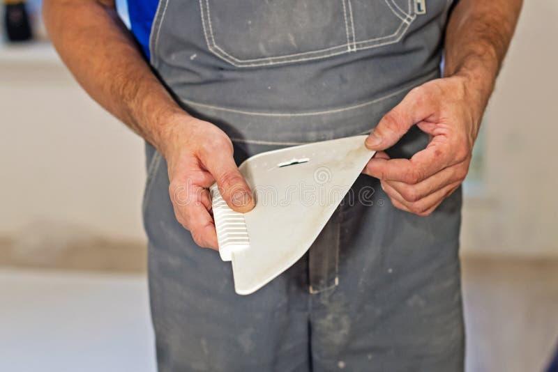 Manos con un raspador para alisar el papel pintado en la pared durante la reparación imagenes de archivo