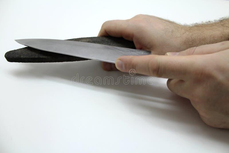 Manos con una muela y un cuchillo imagen de archivo