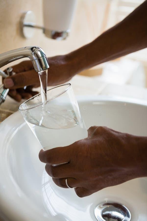 Manos cosechadas del vidrio de consumición de relleno del hombre en el fregadero imagen de archivo