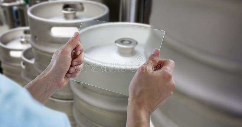 Manos cosechadas que fotografían los barriletes a través del dispositivo transparente en la cervecería imagenes de archivo