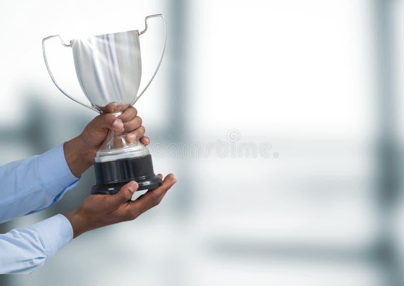 Manos cosechadas que sostienen el trofeo contra fondo defocused imagen de archivo libre de regalías