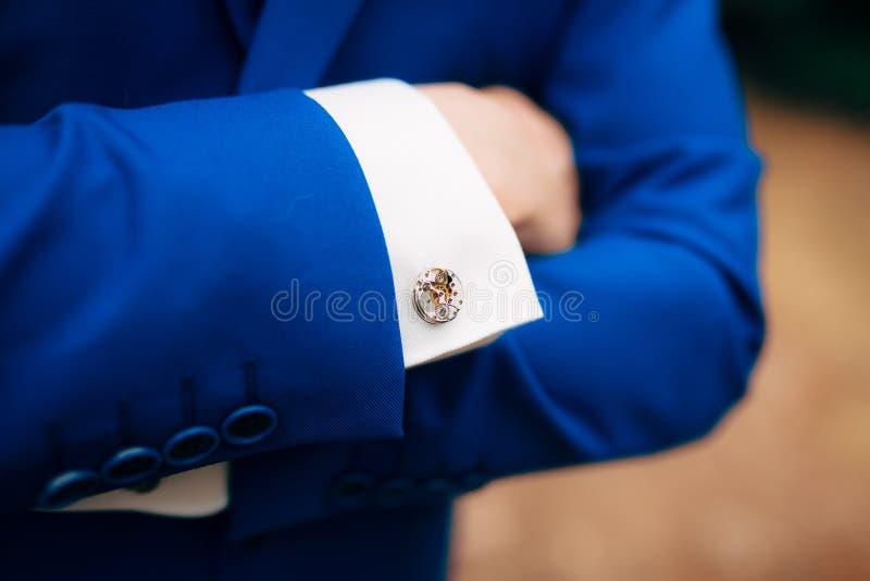 Manos cruzadas del ` s del hombre en su pecho en una chaqueta azul Vínculos de puño franco foto de archivo libre de regalías