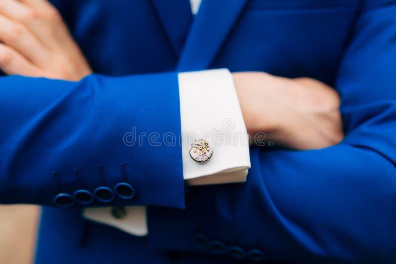 Manos cruzadas del ` s del hombre en su pecho en una chaqueta azul Vínculos de puño franco fotos de archivo