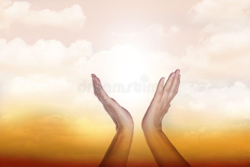 Manos curativas en el cielo con resplandor solar brillante fotografía de archivo