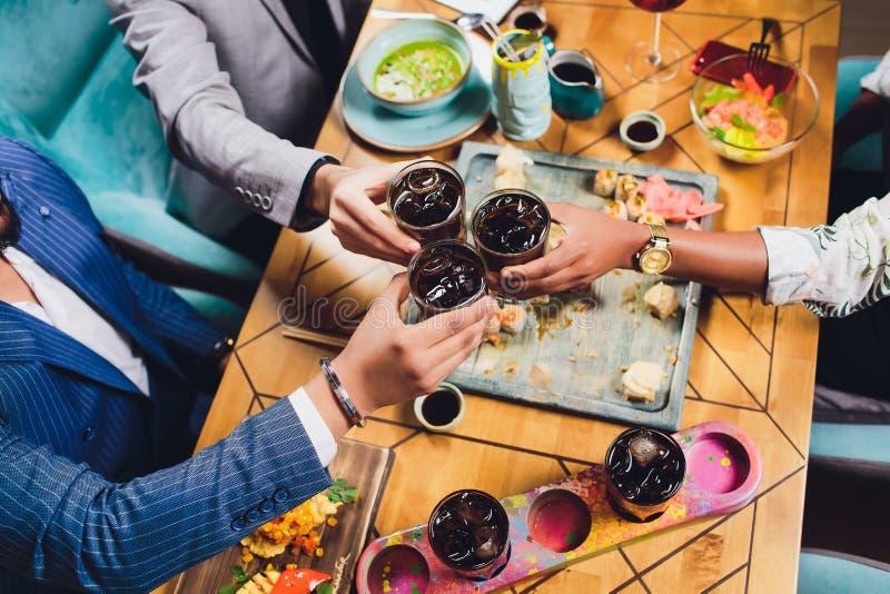 Manos de amigos junto en el c?rculo que sostiene los diversos c?cteles con hielo en el fondo de la tabla de madera vieja foto de archivo