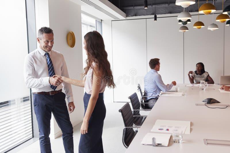 Manos de And Businesswoman Shaking del hombre de negocios en la sala de reunión moderna con los colegas que se encuentran alreded fotos de archivo libres de regalías