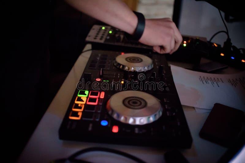 Manos de DJ en cubierta y mezclador del equipo con el disco de vinilo en el partido foto de archivo