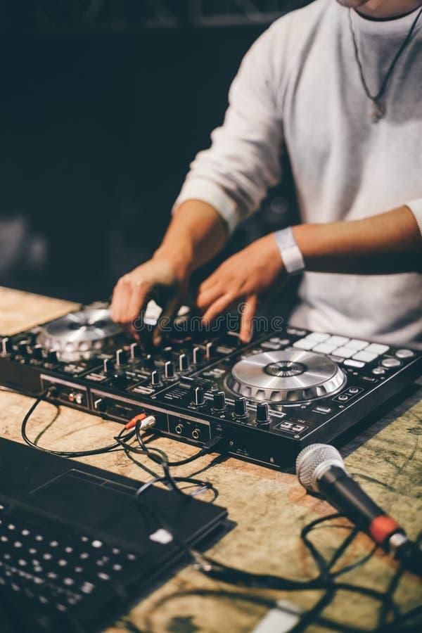 Manos de DJ que juegan música de mezcla en el partido de la noche imagen de archivo libre de regalías