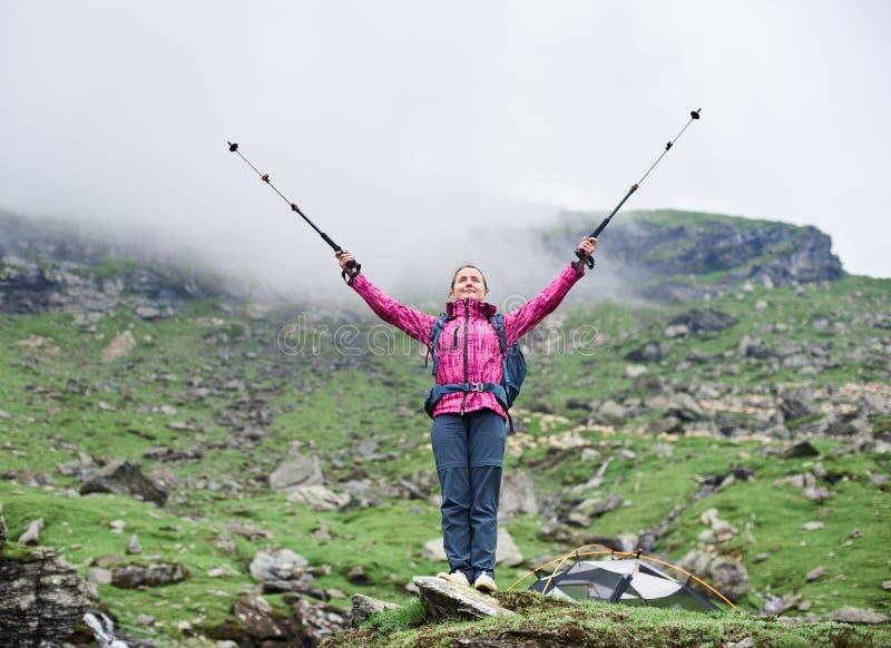 Manos de elevación del escalador femenino hermoso para arriba que admiran la belleza de montañas de niebla rocosas verdes en Ruma fotos de archivo libres de regalías