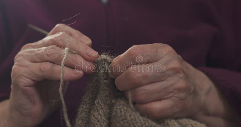 Manos de la abuela del primer que hacen punto el suéter fotos de archivo libres de regalías