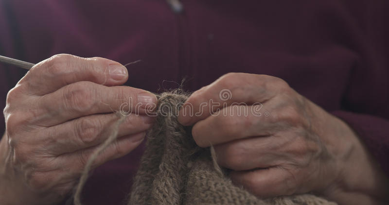 Manos de la abuela del primer que hacen punto el suéter imagenes de archivo