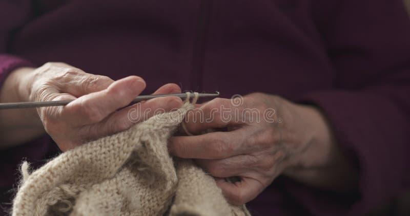 Manos de la abuela del primer que hacen punto el suéter fotografía de archivo libre de regalías
