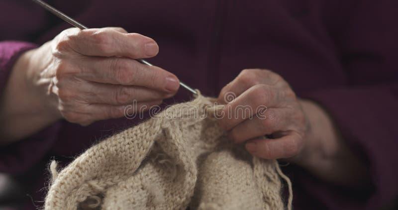 Manos de la abuela del primer que hacen punto el suéter fotografía de archivo