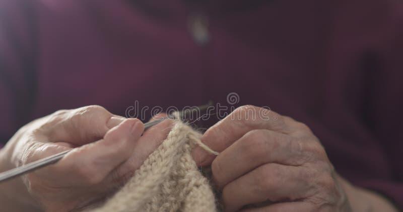 Manos de la abuela que hacen punto el primer del suéter fotos de archivo libres de regalías