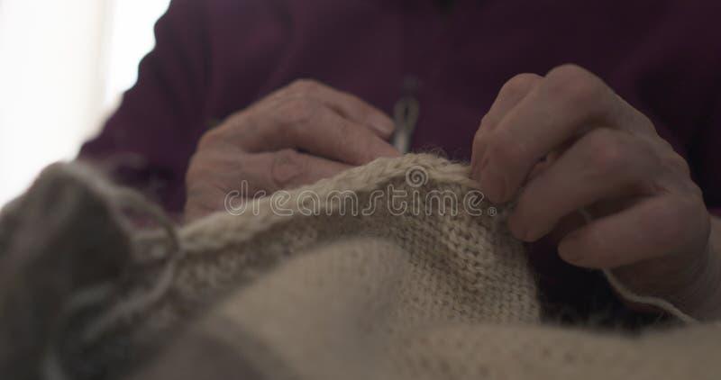 Manos de la abuela que hacen punto el primer del suéter fotos de archivo