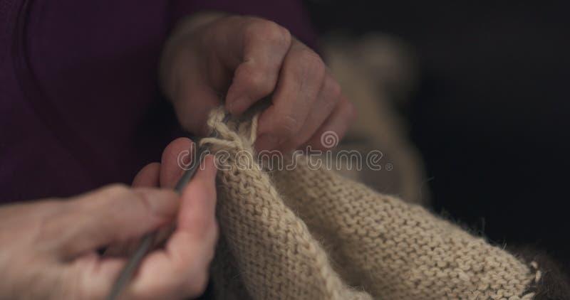 Manos de la abuela que hacen punto el primer del suéter fotografía de archivo libre de regalías