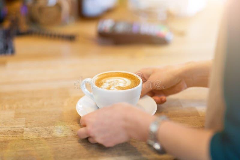 Manos de la camarera listas para servir una taza de café fotos de archivo