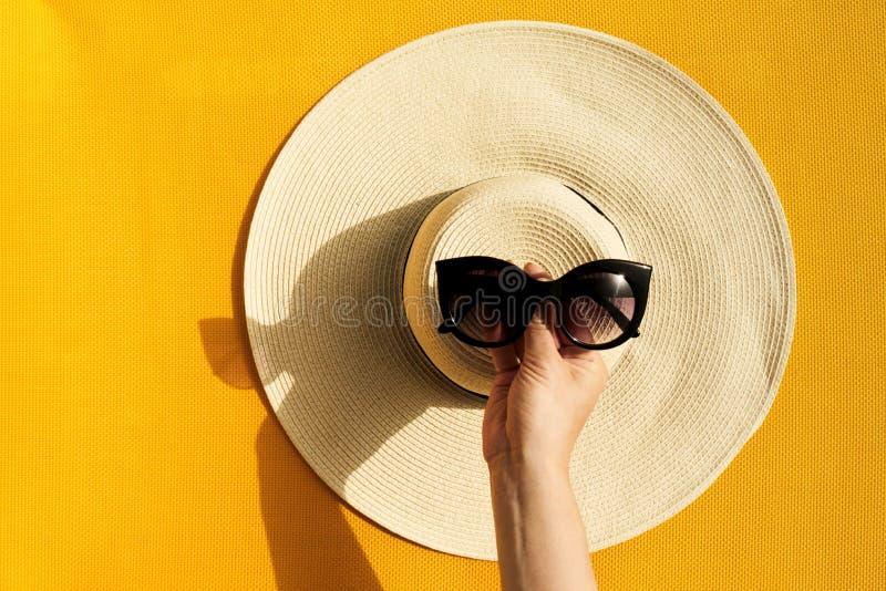 Manos de la chica joven que sostienen las gafas de sol sobre el sombrero de paja en vibran foto de archivo libre de regalías