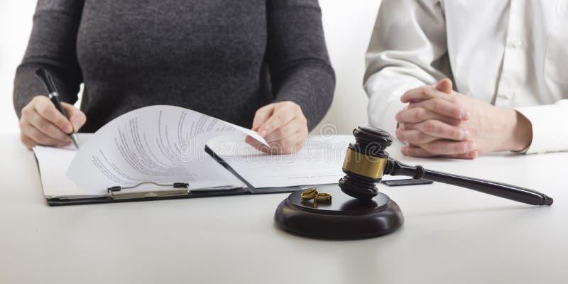 Manos de la esposa, decreto de firma del marido del divorcio, disolución, cancelando boda, documentos de la separación legal, arc foto de archivo