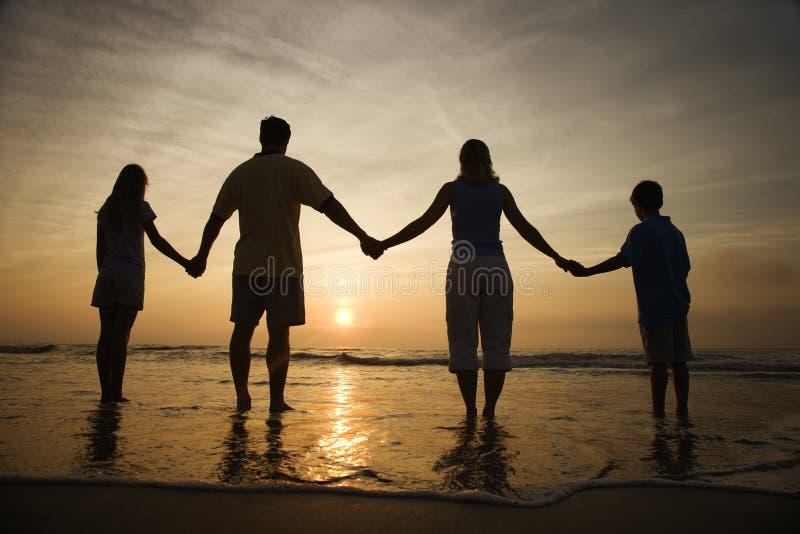 Manos de la explotación agrícola de la familia en la playa que mira la puesta del sol fotografía de archivo libre de regalías