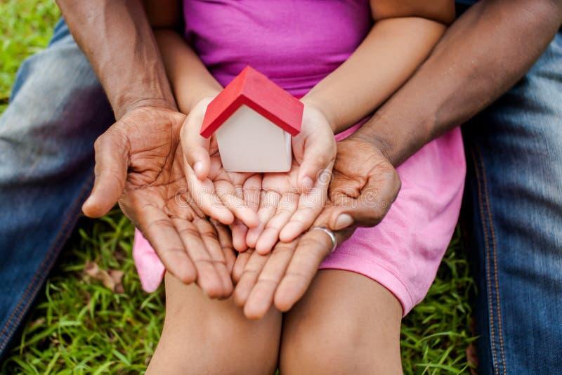 Manos de la familia junto que sostienen la casa en el parque verde - familia ho fotografía de archivo libre de regalías