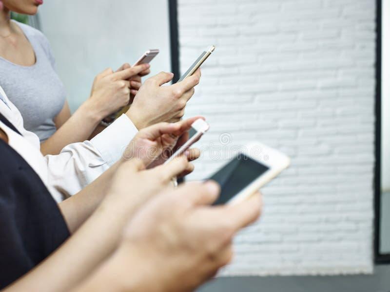 Manos de la gente joven que juega con los teléfonos móviles fotos de archivo