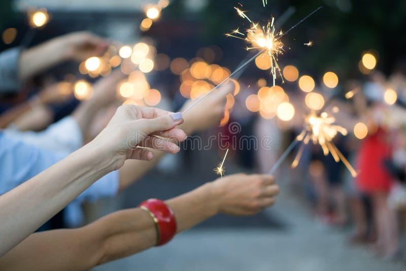 Manos de la gente que sostiene bengalas en un banquete de boda imagen de archivo libre de regalías