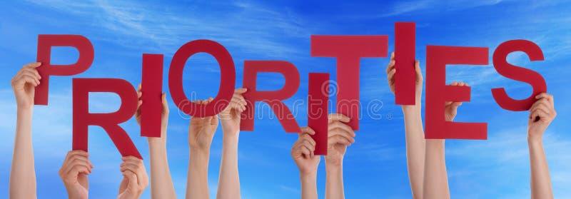 Manos de la gente que sostienen el cielo azul de las prioridades rojas de la palabra imágenes de archivo libres de regalías