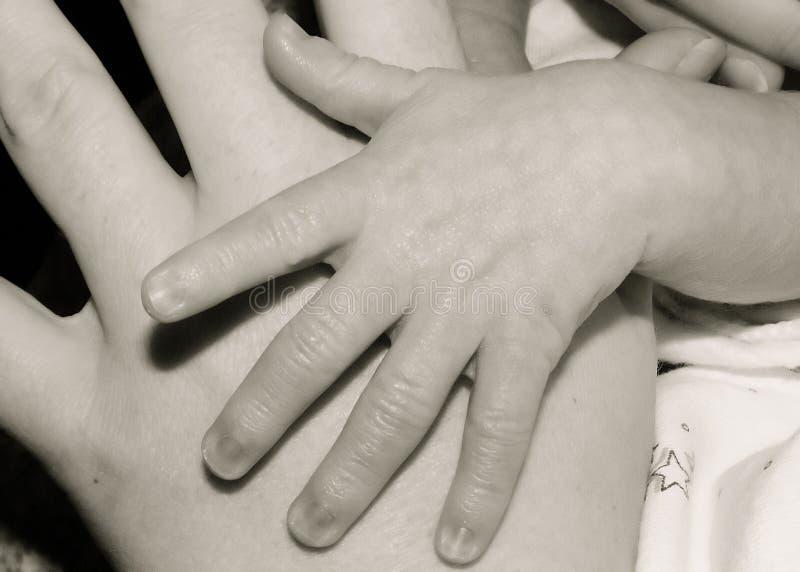 Manos de la madre y del niño foto de archivo