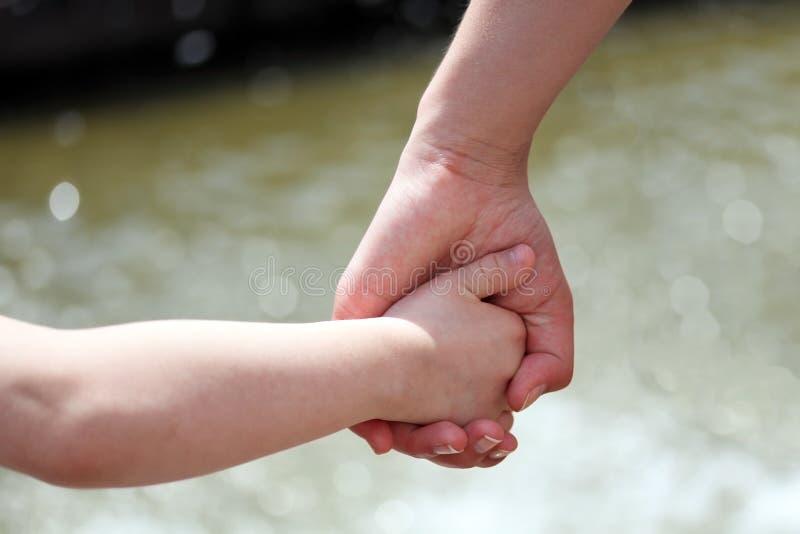 Manos de la madre y del niño imagenes de archivo