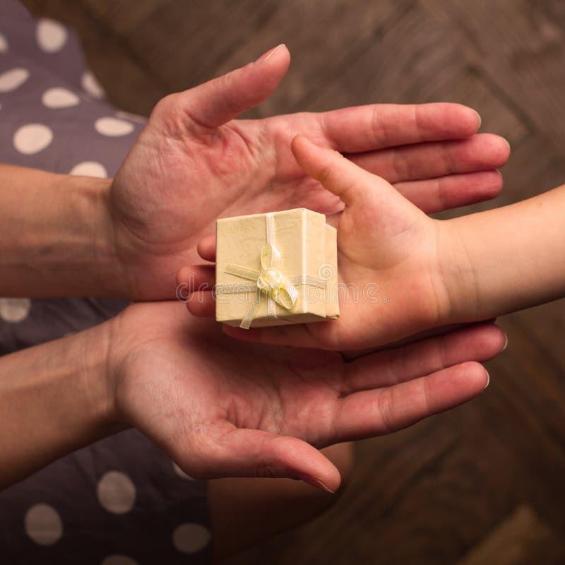 Manos de la madre y del niño que reciben los regalos imagenes de archivo