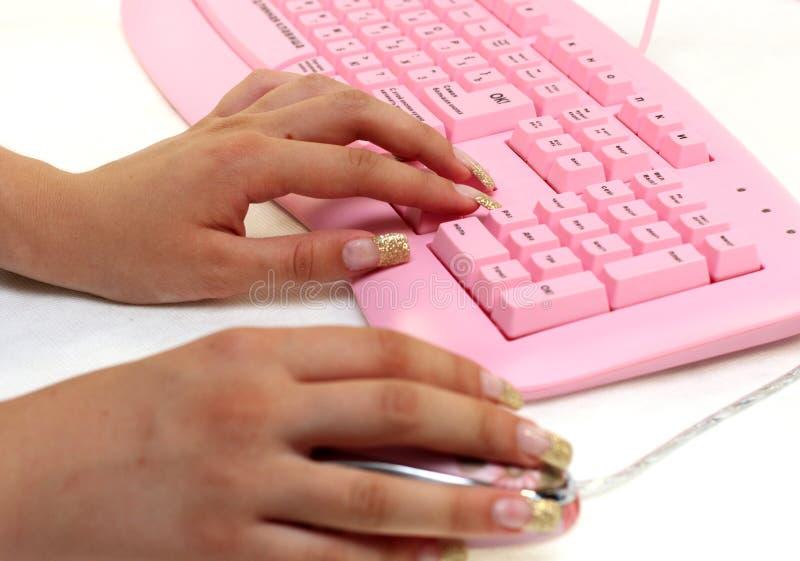Manos de la muchacha en el teclado y el ratón imagenes de archivo