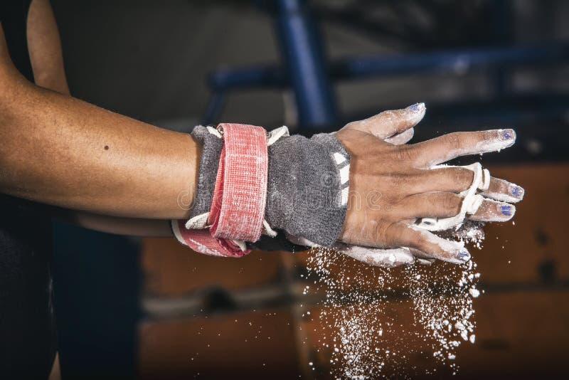 Manos de la muchacha joven del gimnasta con magnesio imagen de archivo