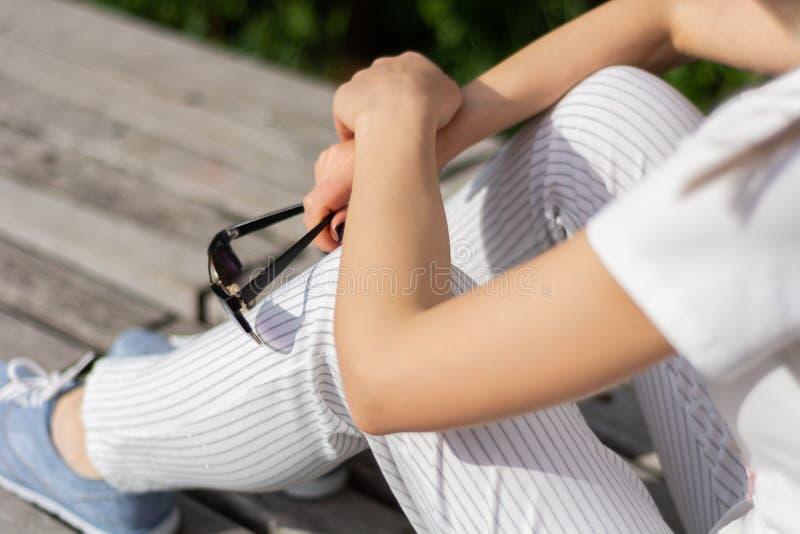 Manos de la muchacha que sostienen las gafas de sol en las piernas con los pantalones rayados y que se sientan en un banco en el  imagenes de archivo