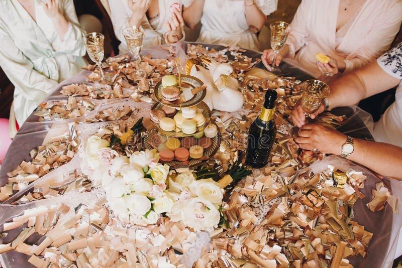 Manos de la muchacha que sostienen los vidrios del champán en la tabla con los macarons deliciosos, el oro y el confeti de plata, fotografía de archivo libre de regalías