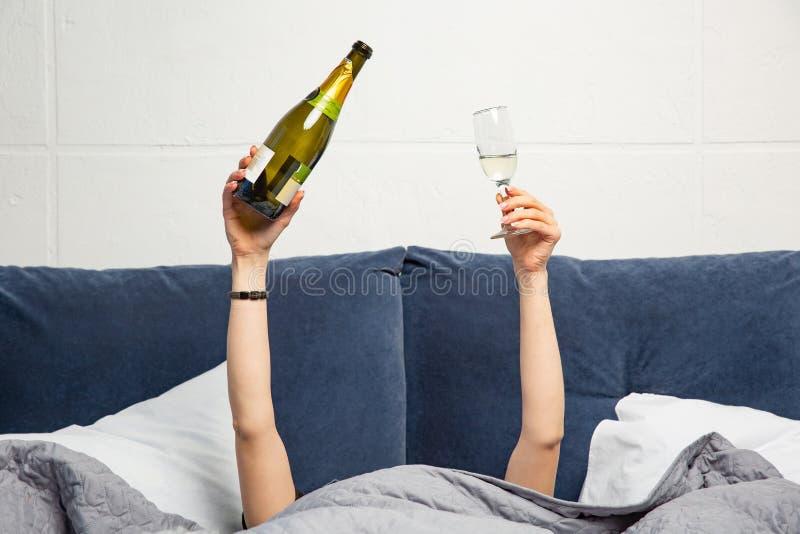 Manos de la mujer con la botella y el vidrio de champán en cama imagen de archivo