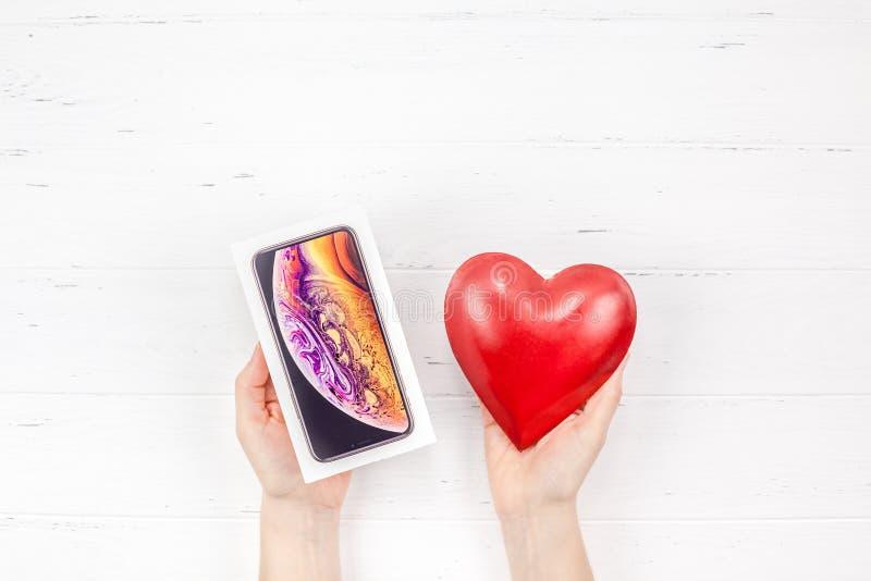 Manos de la mujer con la caja del iPhone XS de Apple y el corazón rojo imagen de archivo