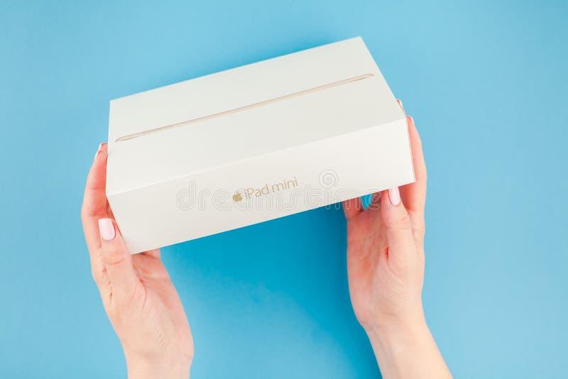 Manos de la mujer con la caja de iPad de Apple mini foto de archivo