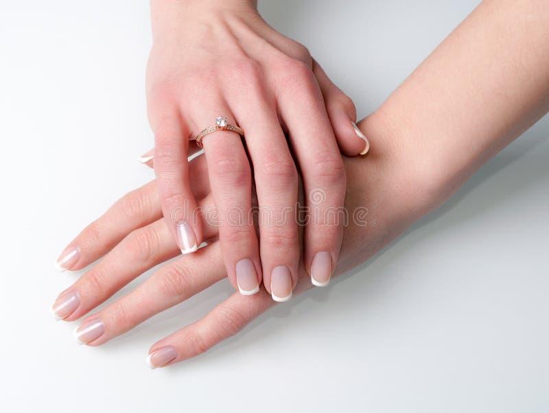 Manos de la mujer con el anillo de compromiso en blanco imagenes de archivo