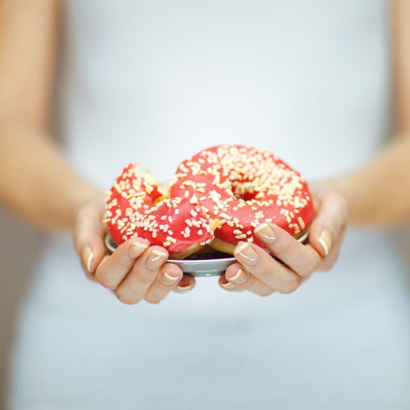 Manos de la mujer con el esmalte de uñas perfecto que sostiene una placa con los anillos de espuma rosados imagenes de archivo