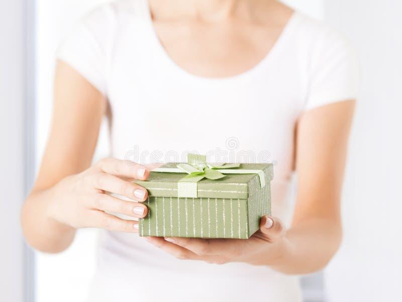 Manos de la mujer con la caja de regalo foto de archivo