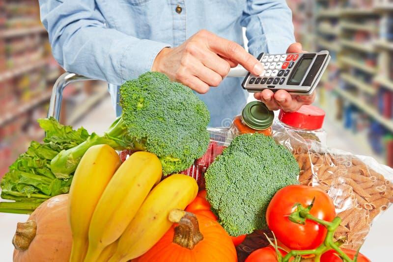 Manos de la mujer con la comida y la calculadora del ultramarinos foto de archivo