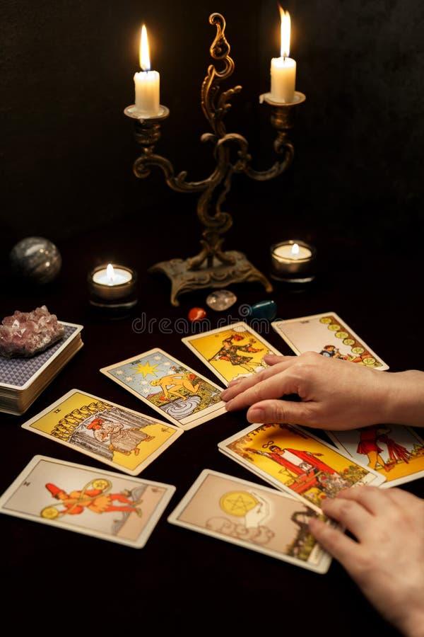 Manos de la mujer con las cartas de tarot foto de archivo