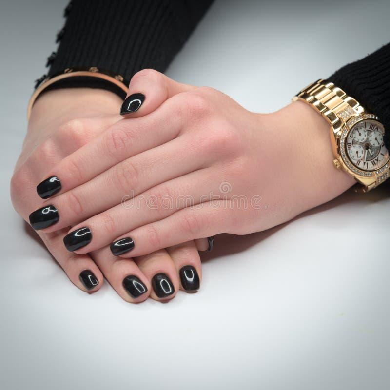 Manos de la mujer con la manicura hermosa en el fondo blanco A mano una pulsera y un reloj del oro foto de archivo