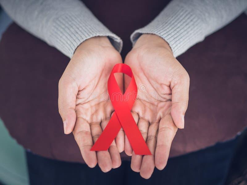 Manos de la mujer del primer que sostienen el VIH rojo de la cinta, fotografía de archivo