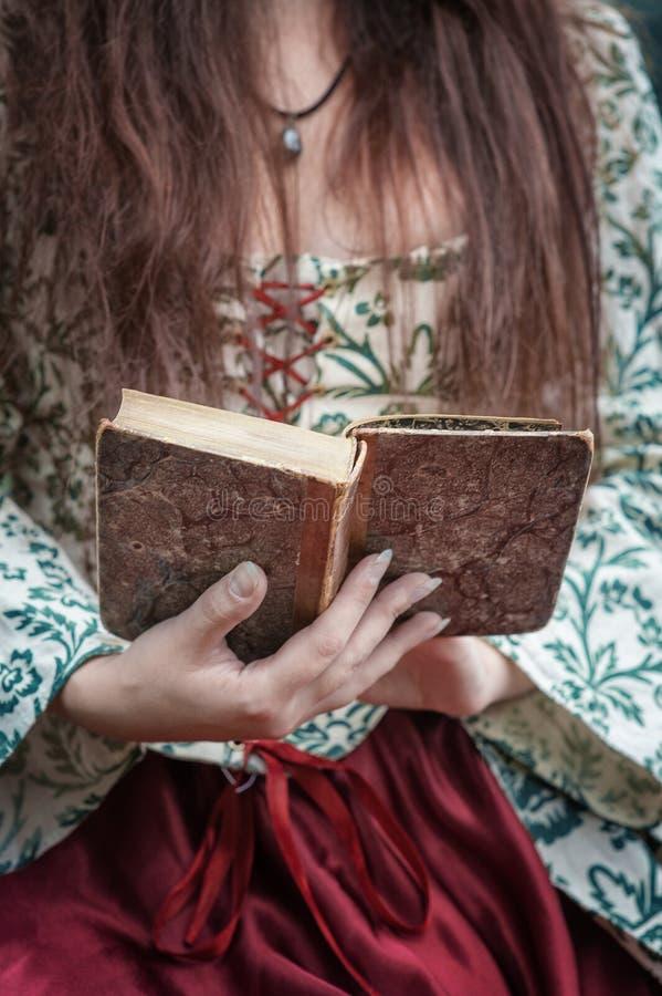 Manos de la mujer en el vestido medieval que sostiene el libro viejo del vintage fotos de archivo libres de regalías