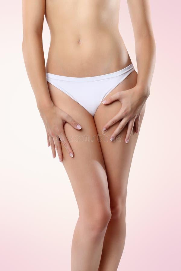 Manos de la mujer en sus piernas en fondo rosado fotos de archivo
