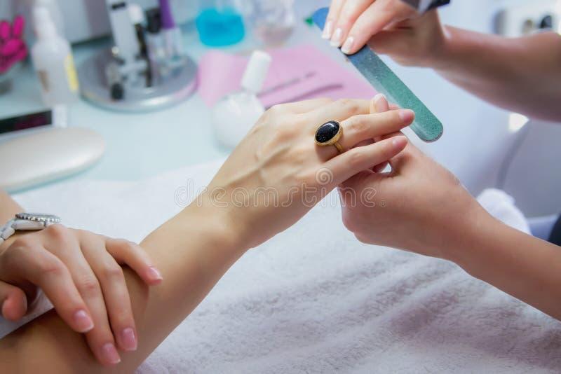 Manos de la mujer en un salón del clavo que recibe una manicura de un cosmetólogo imagen de archivo
